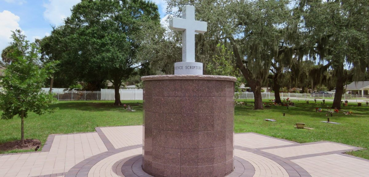 A cross statue in gray granite sits atop a Canterbury columbarium.