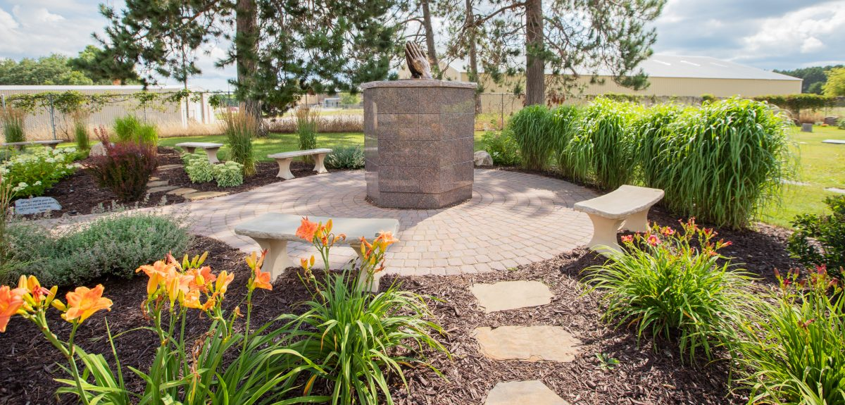 A pathway made of stone pads lead to an Antioch columbarium surrounded by flourishing plantings.