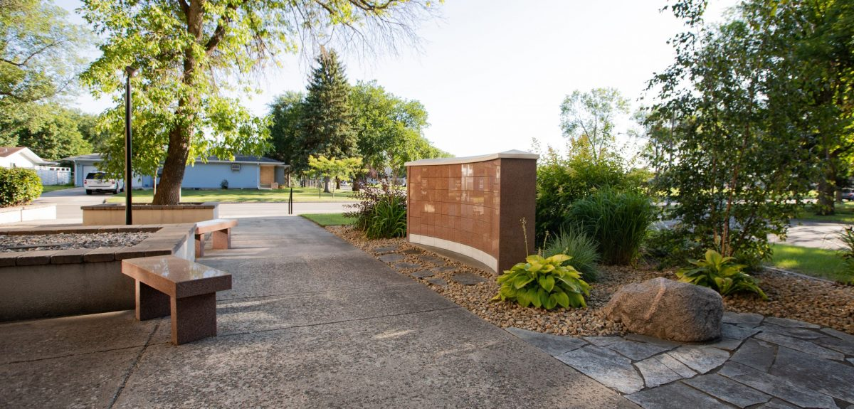A cement sidewalk runs past a columbarium wall with two matching granite benches across from it.