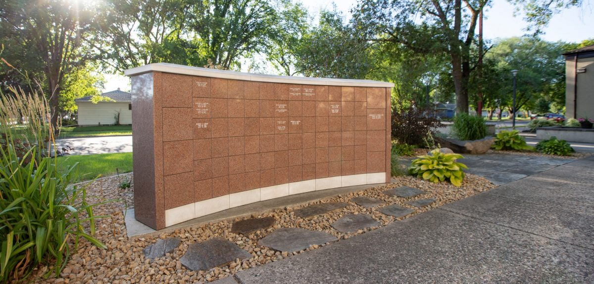 A ray of sun shines brightly though the trees behind a columbarium wall.