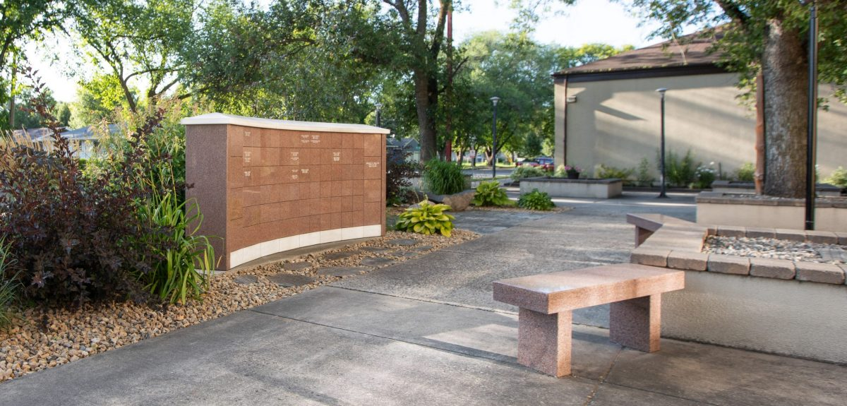 Granite benches and raised garden beds sit across from a columbarium wall surrounded by mature trees that shade the entire area.