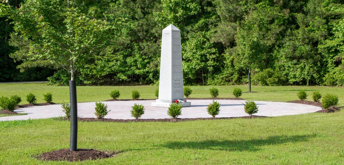 An Obelisk Ossuarium sits on a circular pad of pavers surrounded by plantings.