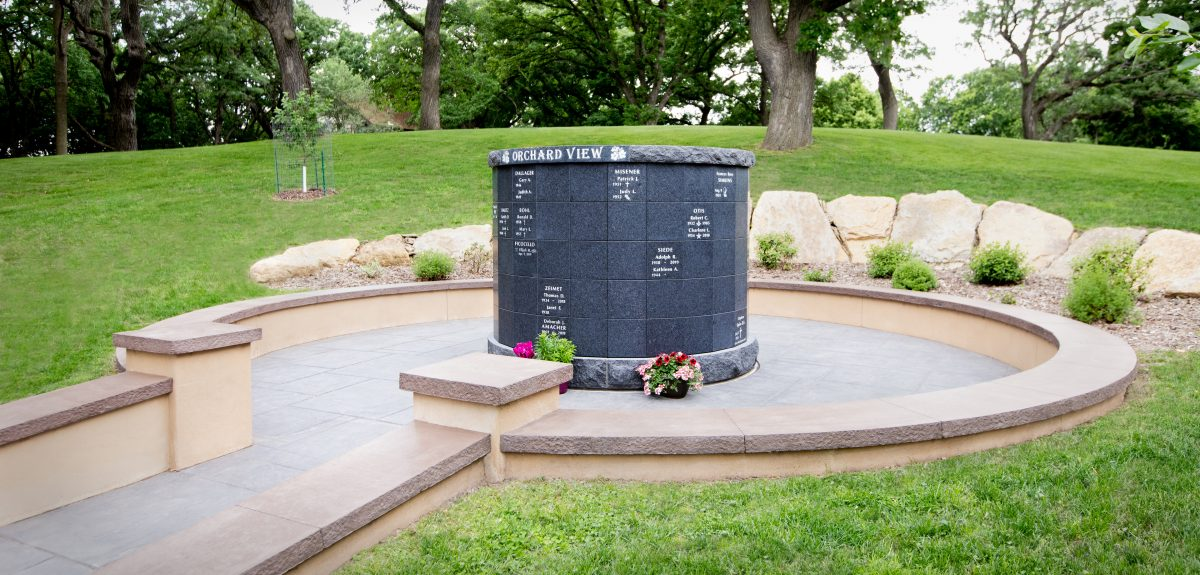 A Pre-Assembled York columbarium is set below grade surrounded by a low wall and many large landscaping rocks.