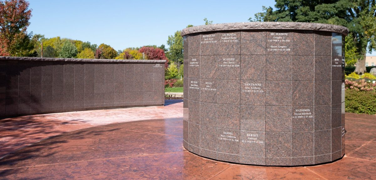 A York columbarium with multiple inscriptions sits across from a radiused columbarium wall atop a rich, red, concrete pad.