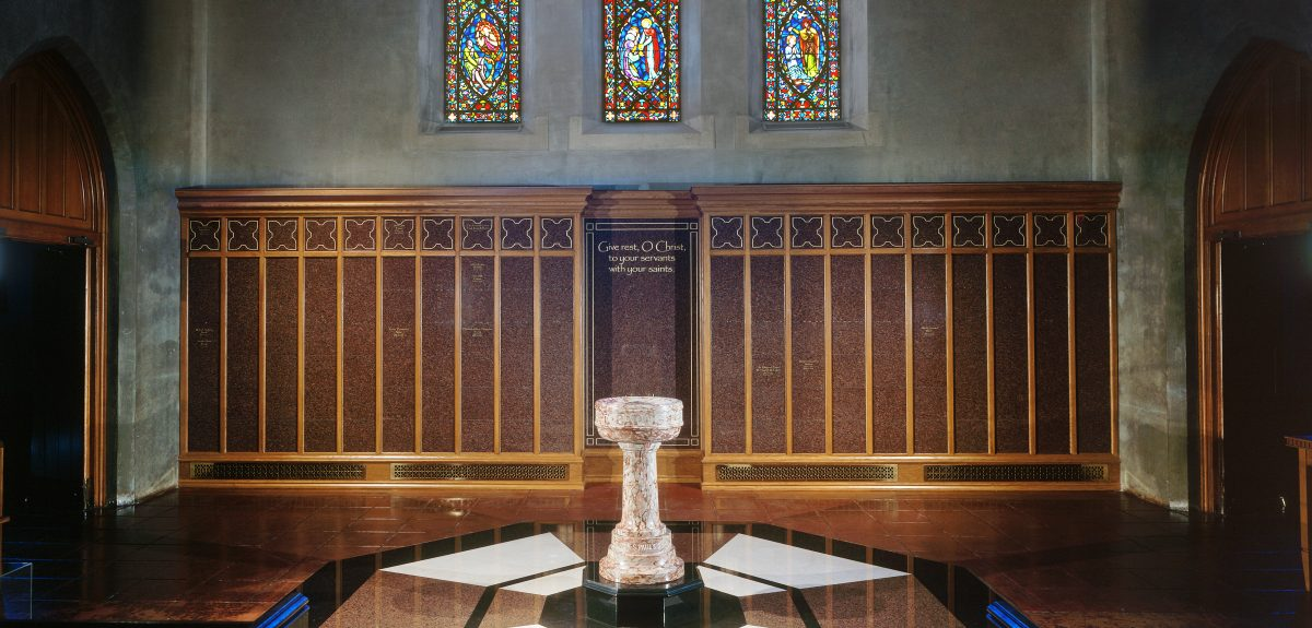 A holy water font sits in front of a columbarium wall under three stained glass windows.