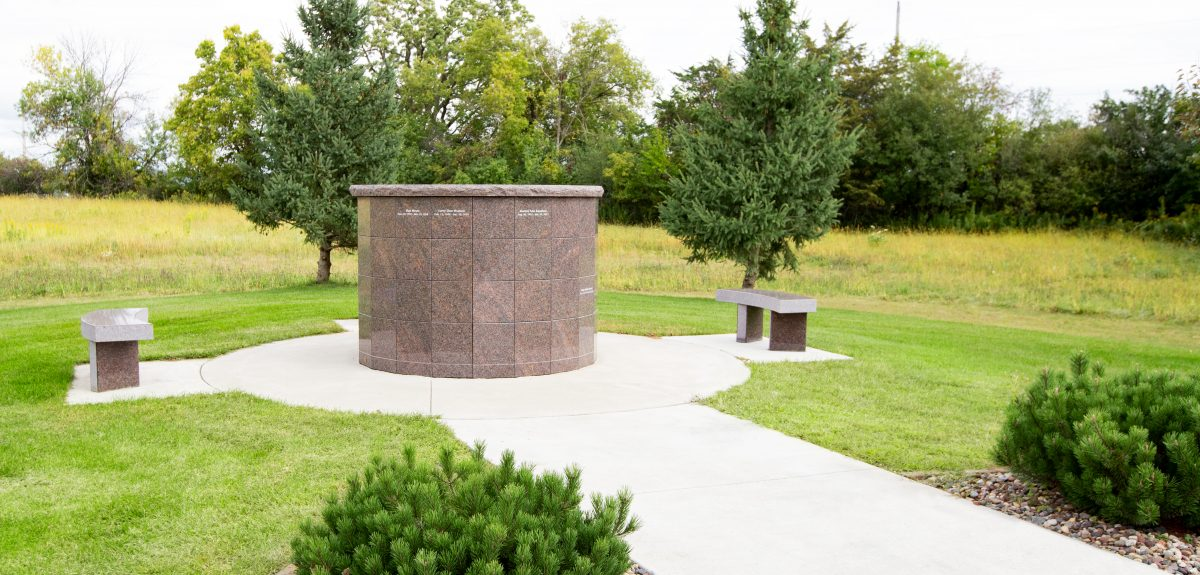 A Canterbury columbarium and matching granite benches sit in front of a tree line.