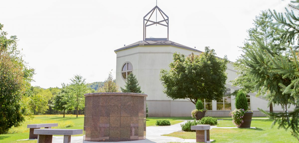 A Canterbury columbarium is surrounded by three matching curved granite benches in front of a church.