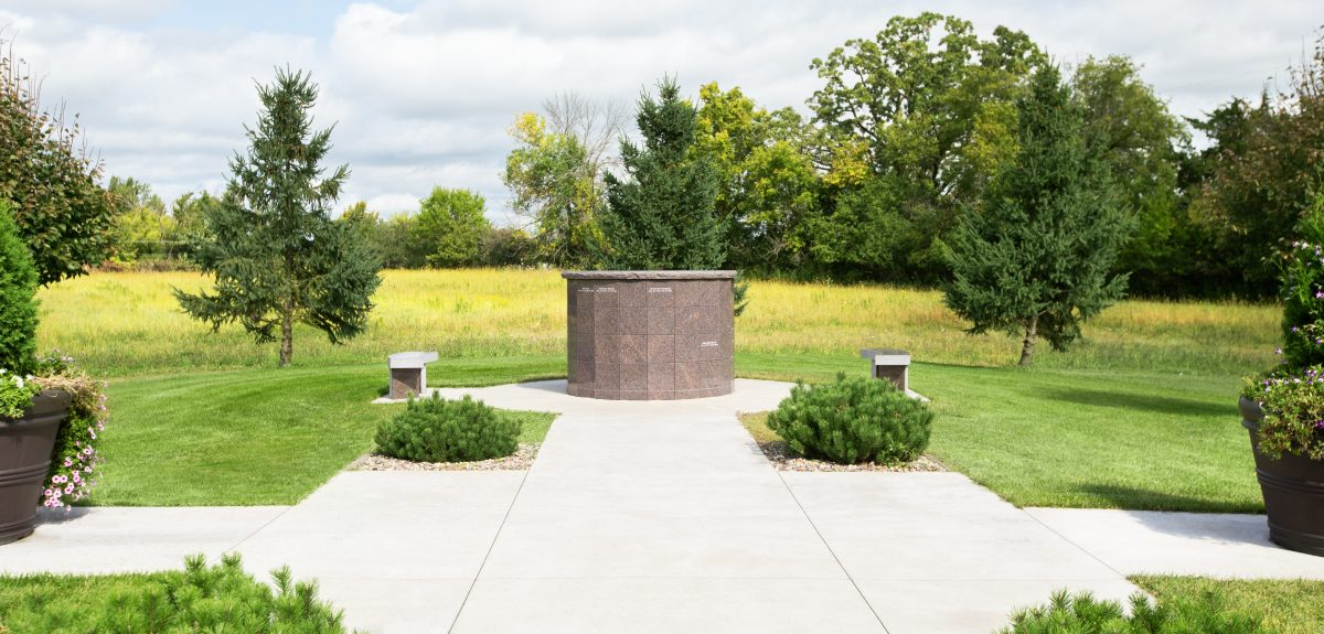 A columbarium lies at the end of a concrete path adorned by bushes and flower planters.