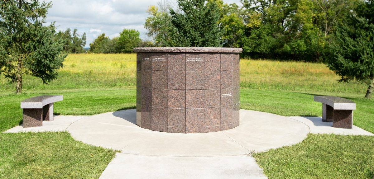 A columbarium sits on a concrete pad in a grassy area.