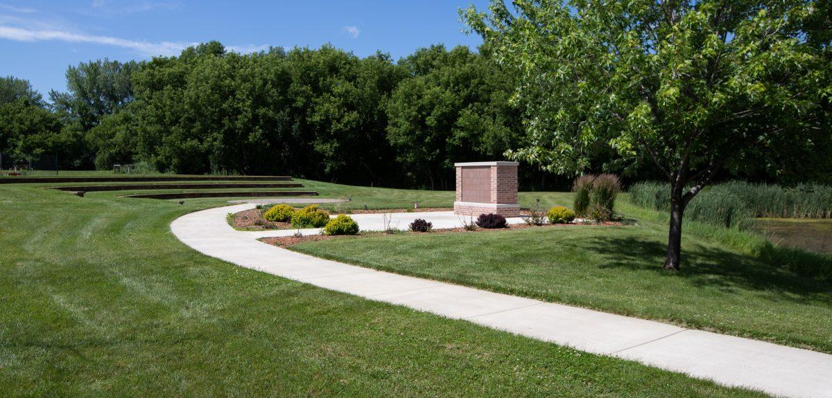 A rectangular columbarium sits just off of a curved concrete path near a pond.