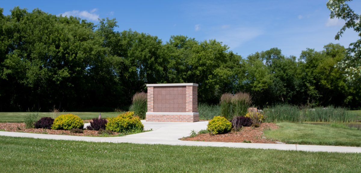 A rectangular columbarium cased in brick masonry sits on a concrete pad surrounded by well manicured bushes.