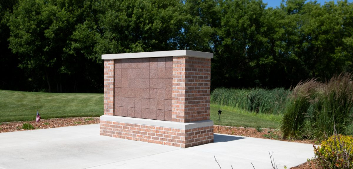 Sun shines brightly on a rectangular columbarium that stands in front of a lush green tree line.