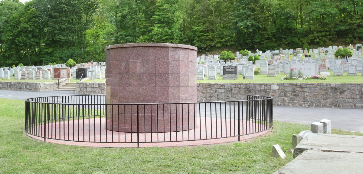 A columbarium sits in front of a stone wall and numerous headstones.