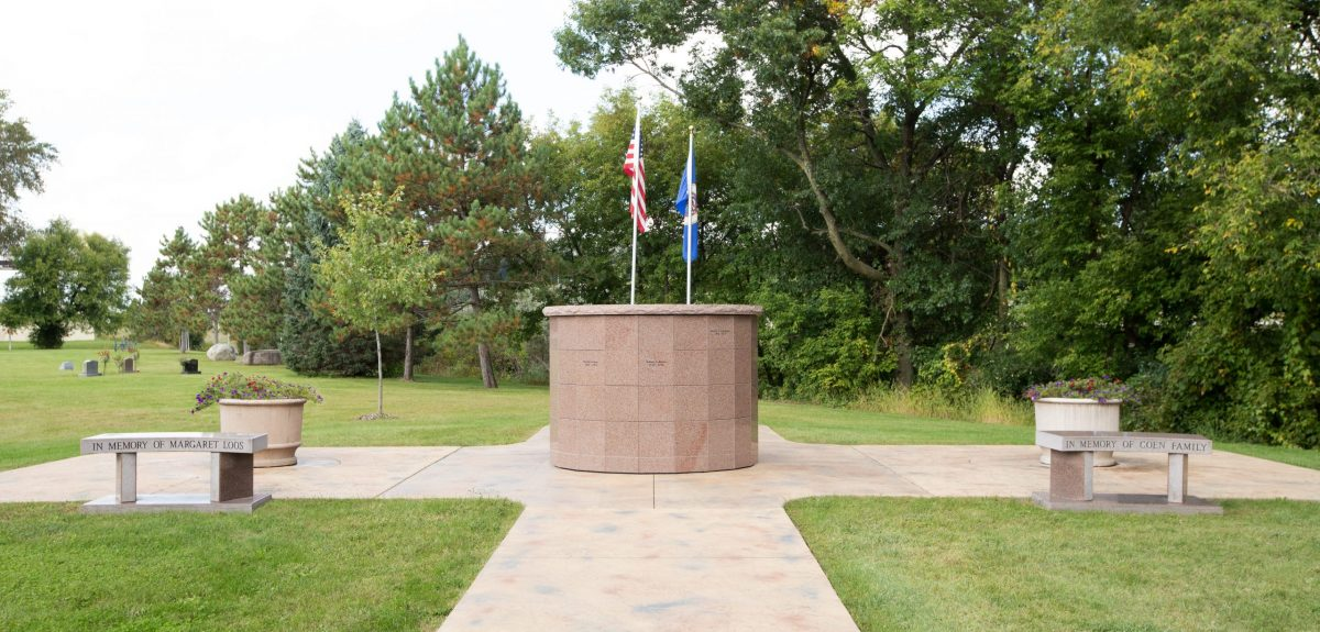A Canterbury columbarium, with a bench and large planter on either side, sits in front of two flag poles and a dense tree line.