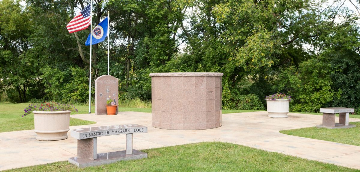 A memorial granite bench sits near a Canterbury columbarium surrounded by two planters, two flagpoles and an additional memorial bench.