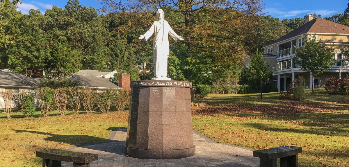 A Welcoming Christ statue sits atop a Pedestal columbarium and casts a long shadow in the sunlight.