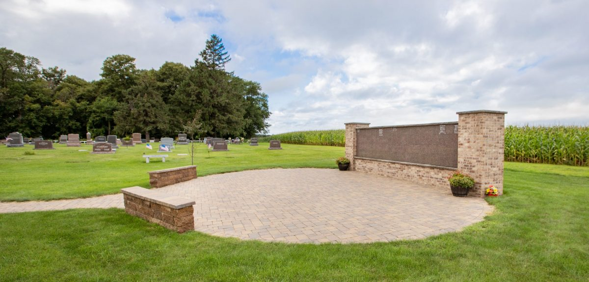 Headstones and a field of corn are seen just beyond a columbarium wall and its matching benches.