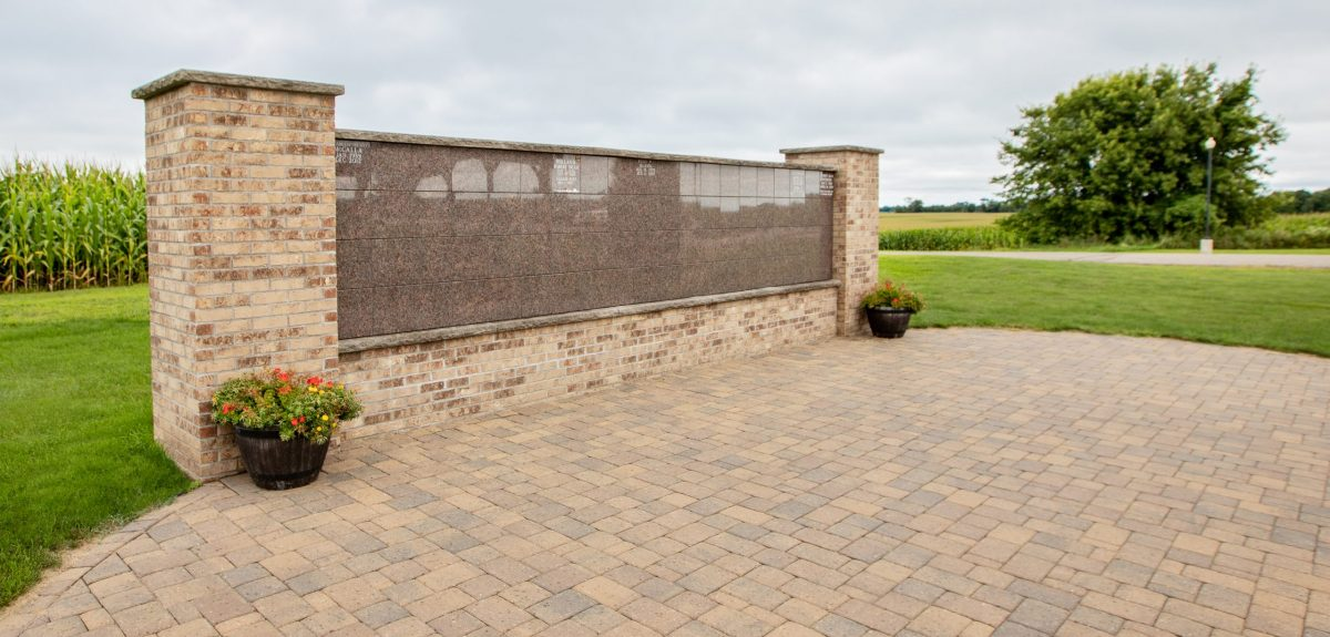 A large pad of pavers lie in front of a columbarium wall under an overcast sky.