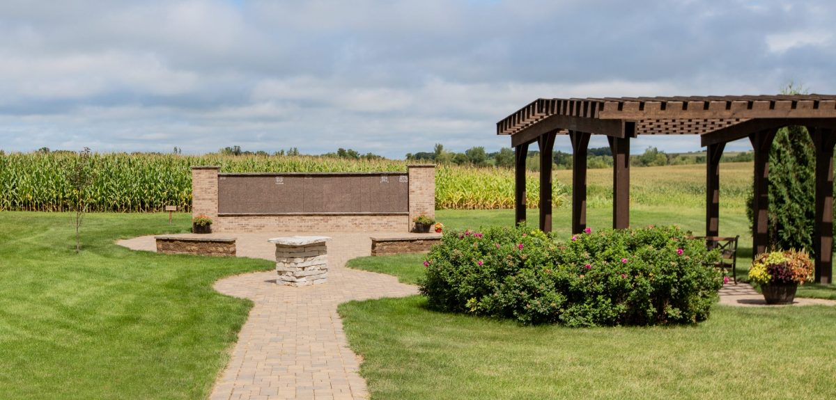 A pergola sits to the right of a columbarium wall at the end of a stone path.