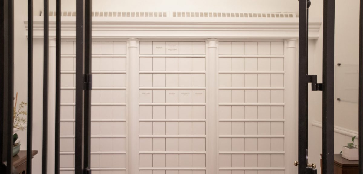 Three columarium cabinets finished in white are separated with elegant columns and adorned with ornate crown molding.