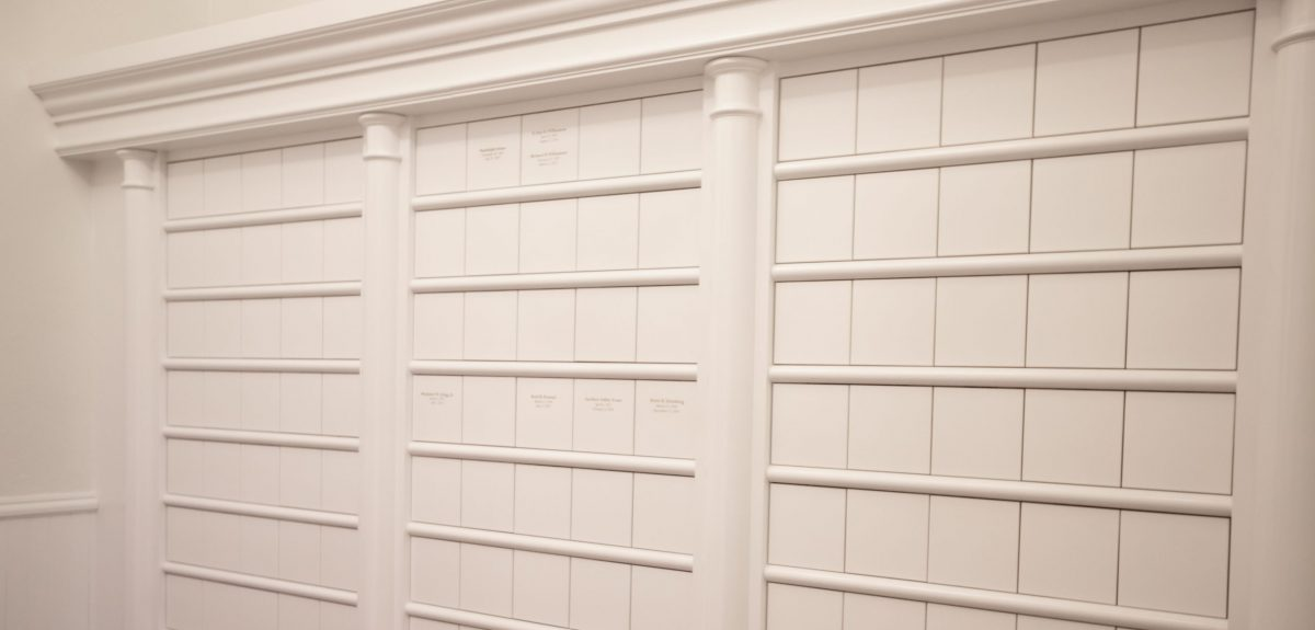 Four tuscan columns uphold substantial crown molding above a wall of columbaria.