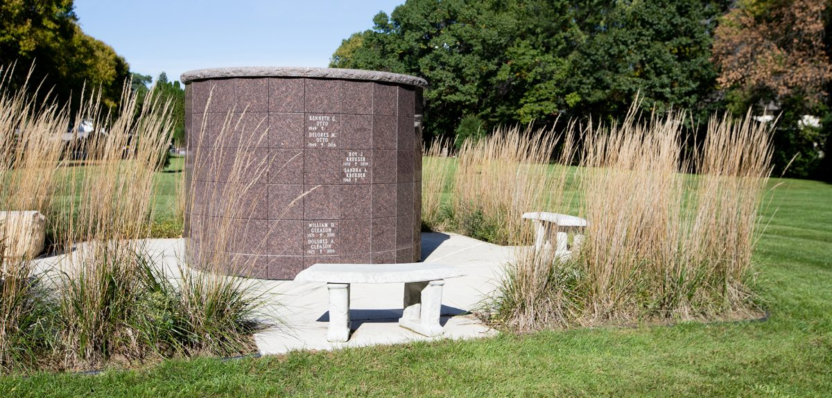 A concrete bench sits in front of a York columbarium surrounded by decorative plantings of feather reed grass.