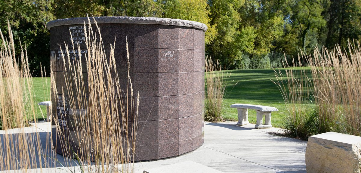 The sun illuminates one side of a York columbarium and draws long shadows from nearby benches and plantings.
