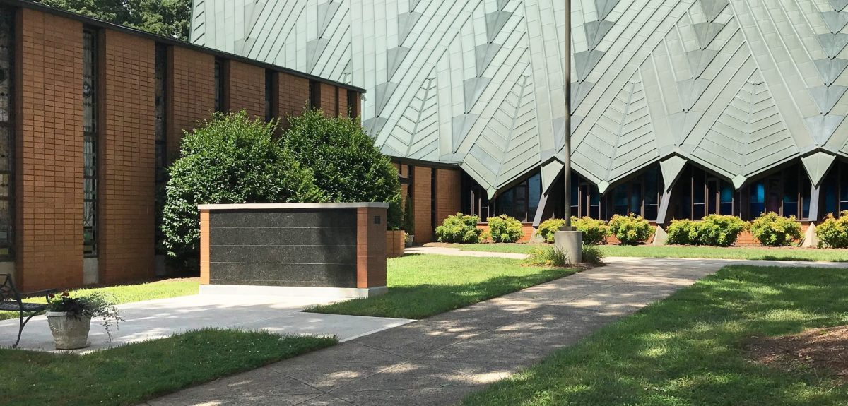 A columbarium wall adorned with a bench and planter sits to the left of a shaded sidewalk