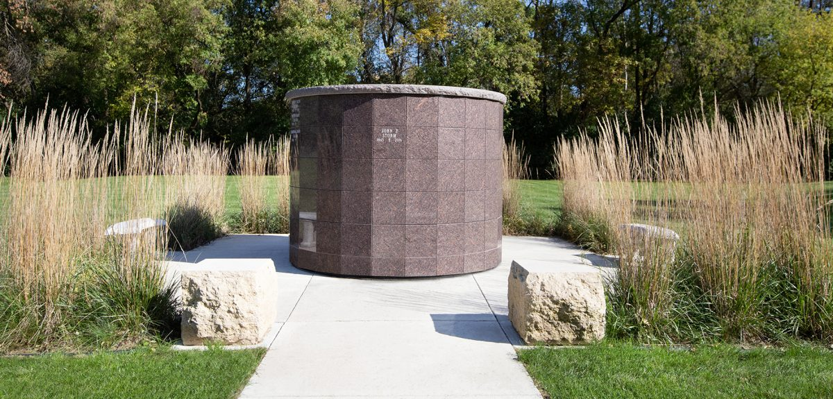 A cement sidewalk leads to a Pre-Assembled columbarium and is adorned with two rough cut stone blocks.