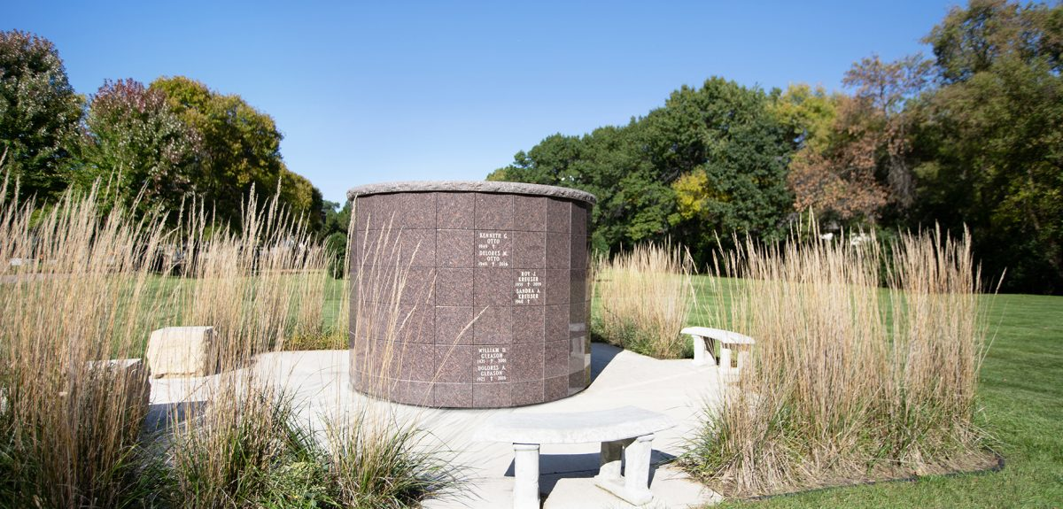 A bright blue sky floats above a grassy clearing that contains a pronounced memorial space.