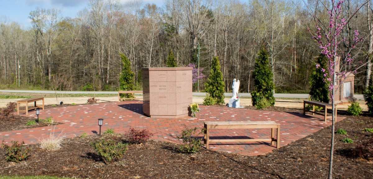 Wooden benches, various plantings, and an angel statue are placed strategically around an Antioch columbarium.