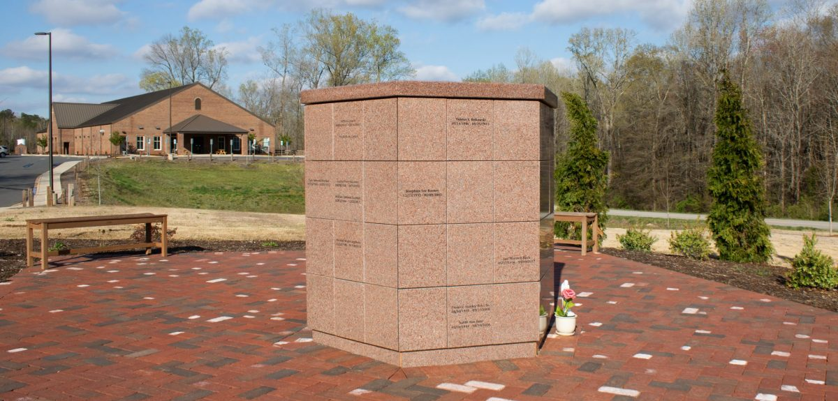 A church building and dense wooded area create the backdrop for a memorial space paved in multicolored bricks.