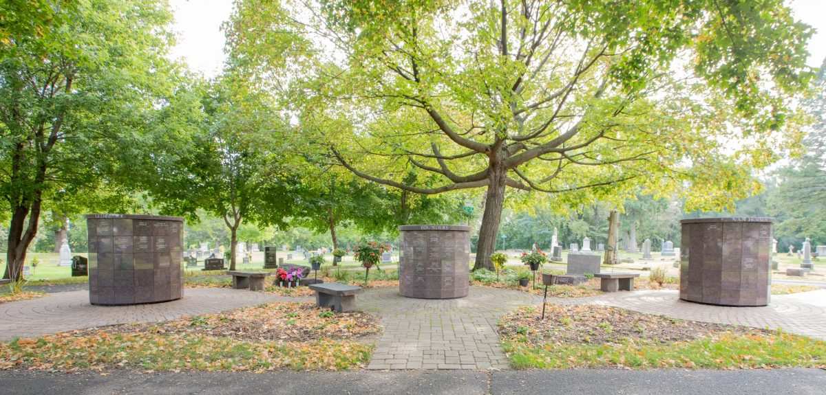 Large lush trees shade three Winchester columbaria in a cemetery.