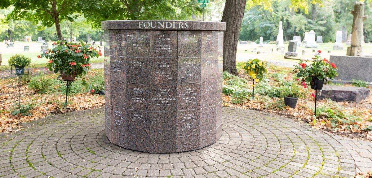 A Winchester columbarium with multiple inscriptions sits at the center of a pad of pavers.
