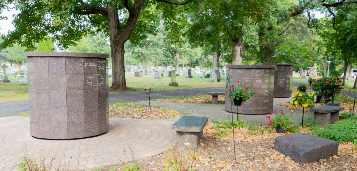 A full cemetery lies behind three Winchester columbaria adorned with various plants and stone benches.