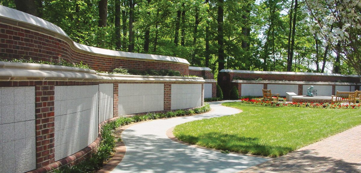 Lush trees cast shadows across a curved columbarium wall framed with red brick masonry.
