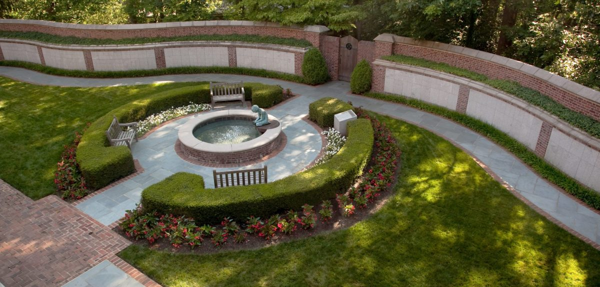 Sweeping curved columbarium walls and a tranquil memorial fountain are seen from an elevated perspective.