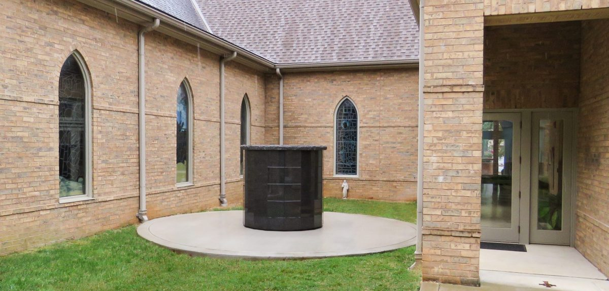 Gothic stained glass windows look onto a Winchester columbarium located in a small courtyard.