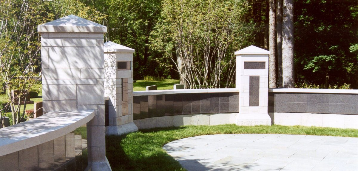 A serpentine wall of columbarium niches is accented with tall stone columns.