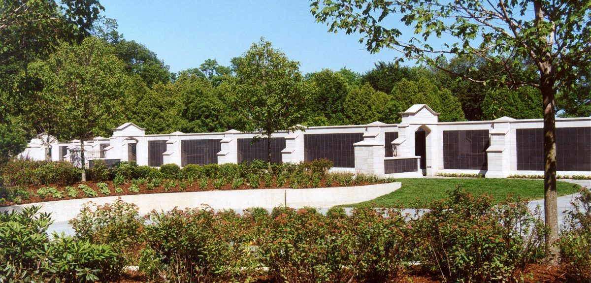 Lush plantings amid small hills precede a formidable wall of columbaria.