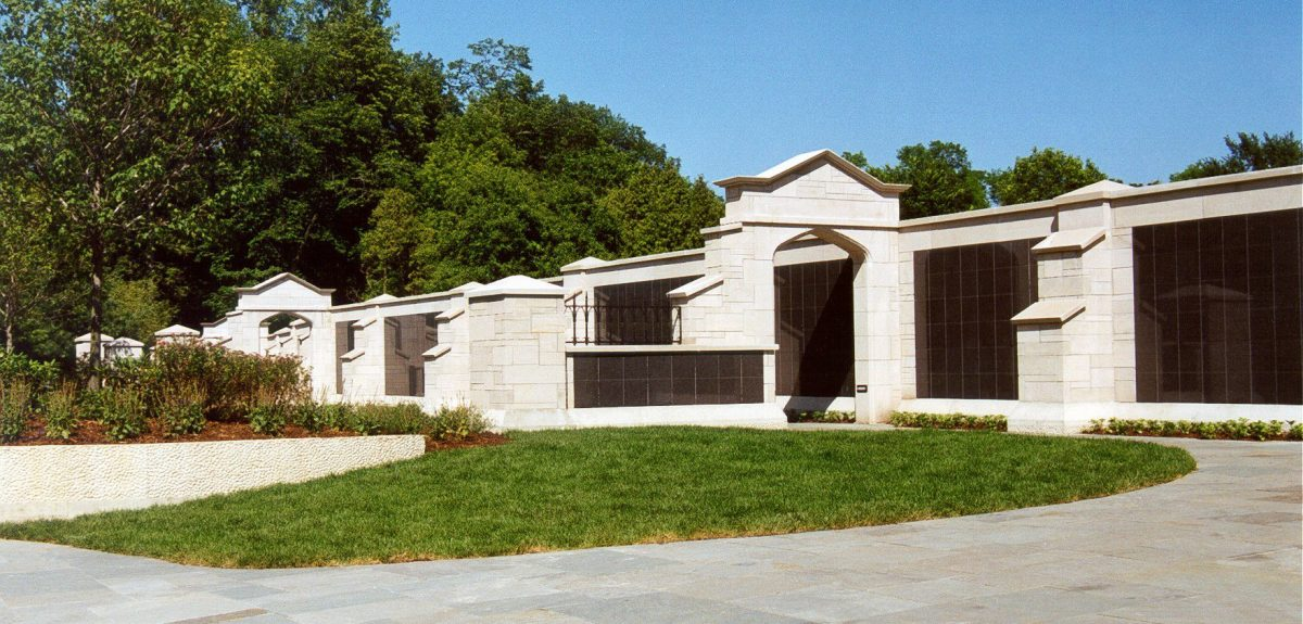 A large stone archway forms a bridge between two walls of columbaria.
