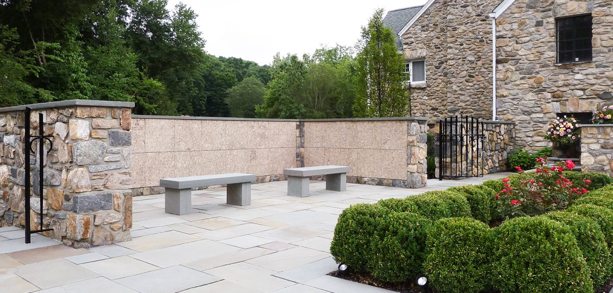 Well manicured hedges are planted directly across from a u-shaped columbarium wall in a church courtyard.