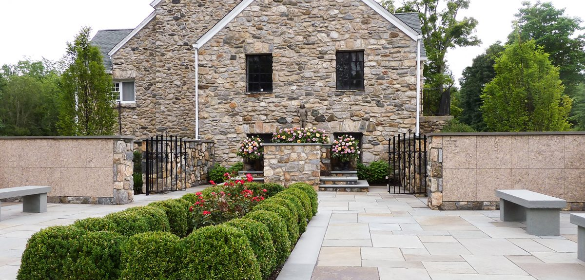 A church courtyard contains symmetrical layout of hedges, stone benches, and columbarium walls.