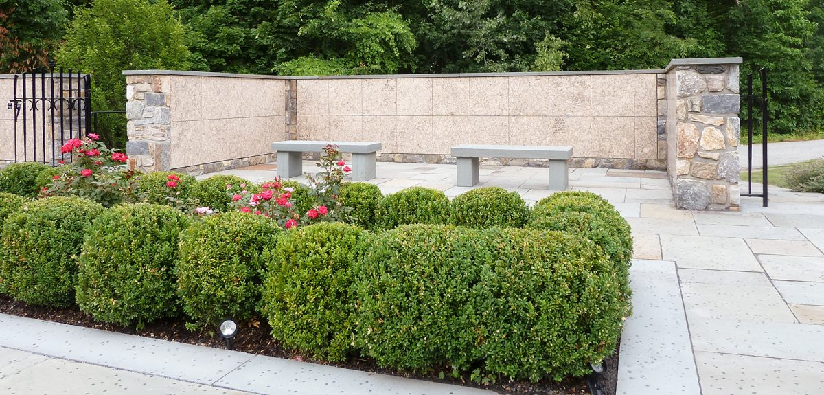 Two benches made of stone face a columbarium wall just beyond a short row of hedges.