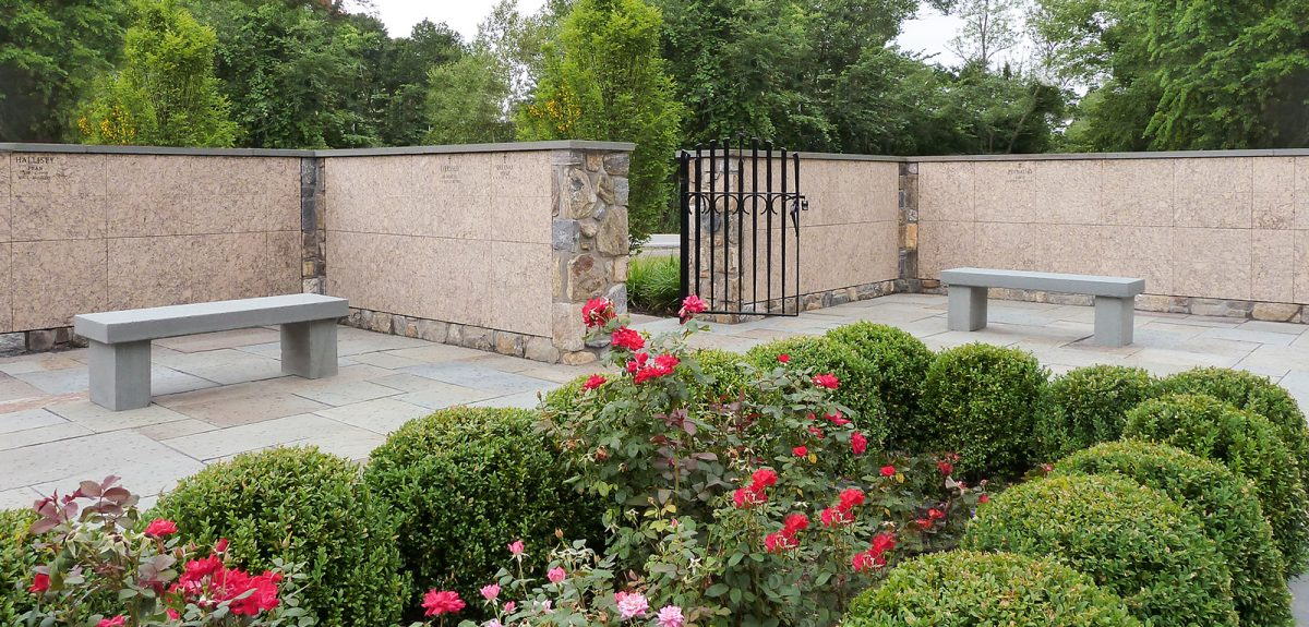 Multiple columbarium walls are seen from the center of a church courtyard where short hedges encapsulate blooming floral pantings.