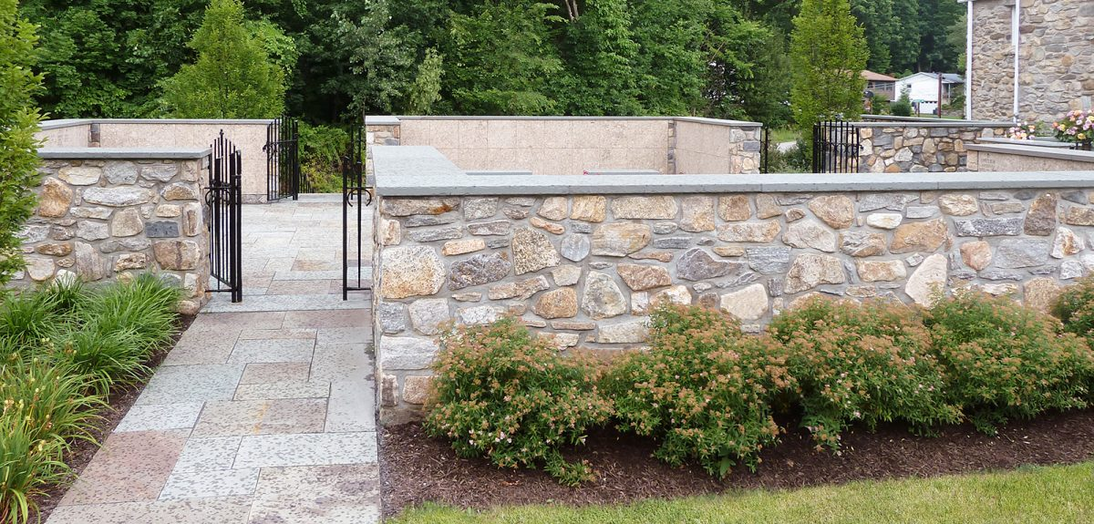 A sidewalk made of rectangular stones leads to an open ornate gate that gives access to the memorial courtyard.