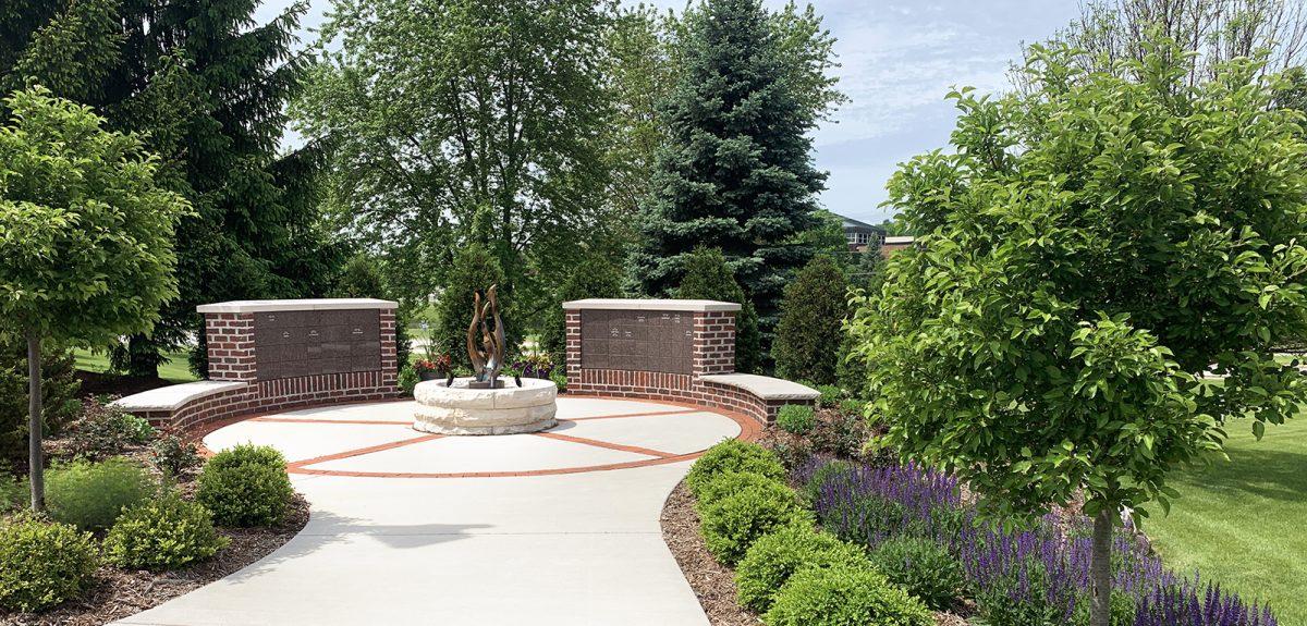 Two curved columbarium walls face inward toward a central lit sculpture.