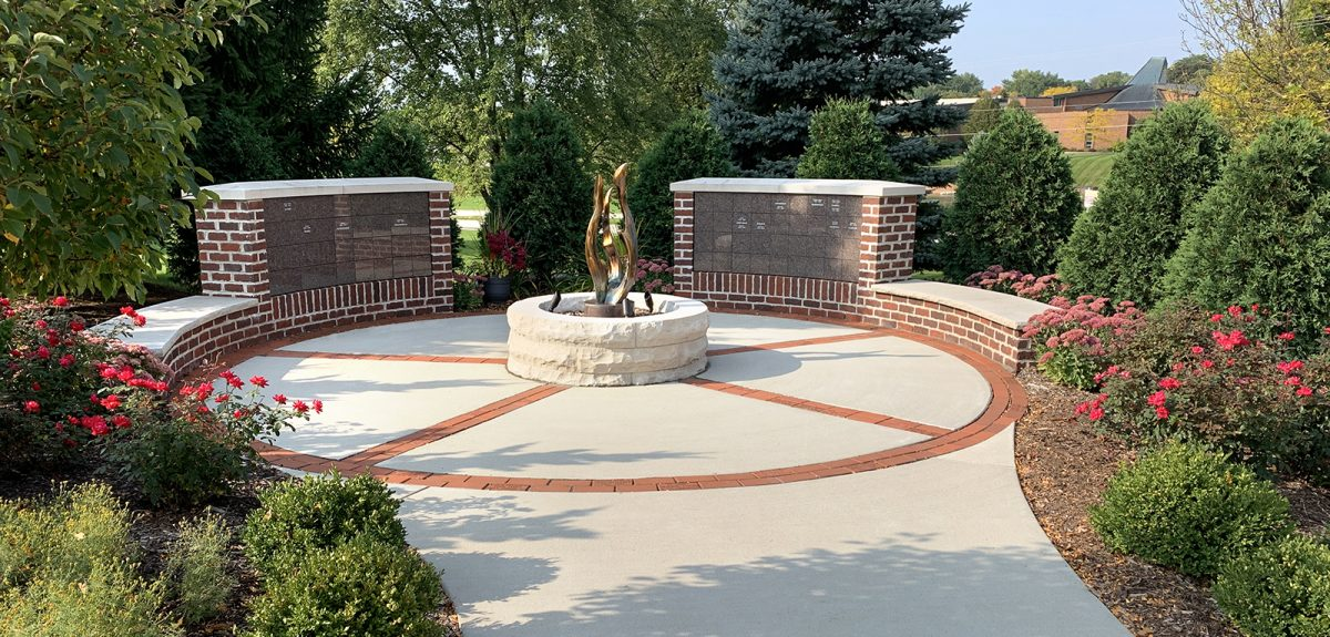Red flowers bloom all around a circular memorial space with an attractive arrangement of memorial pavers.