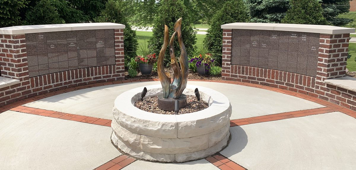 Columbarium walls clad in mahogany granite and surrounded by brick masonry face a raised bed of rock and a golden statue.