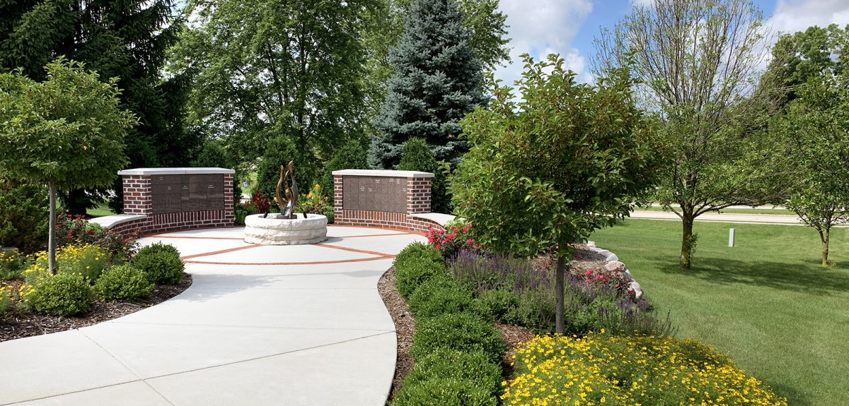 A wide pathway with many attractive plantings on either side ends at the foot of two curved columbarium walls.